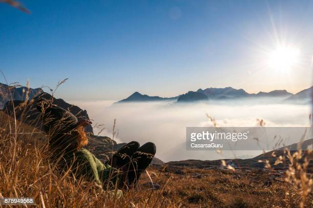 Active Woman Relaxing On The Mountain Meadow With The Amazing View