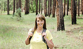 Middle aged woman with COPD hikes in the forest using portable oxygen therapy