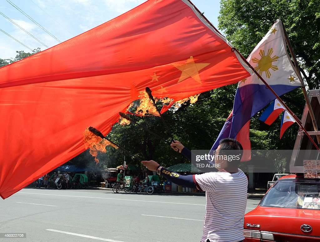 Activist and former policeman Abner Afuang burns a Chinese flag during a protest in front of the national press club building in Manila on June 9...