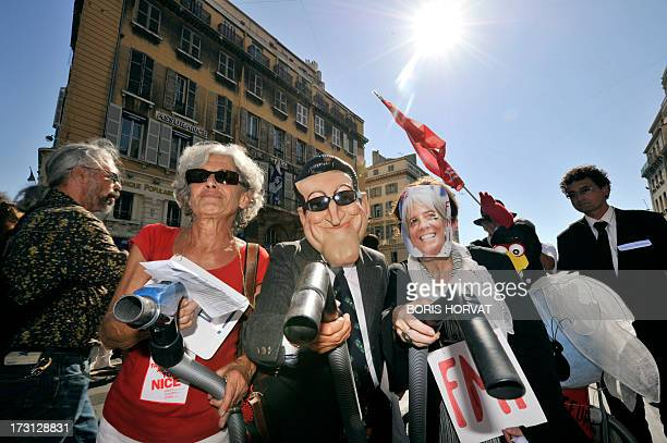 Activist group members wearing caricature masks of French President Sarkozy and International Monetary Fund Managing Director Christine Lagarde hold...