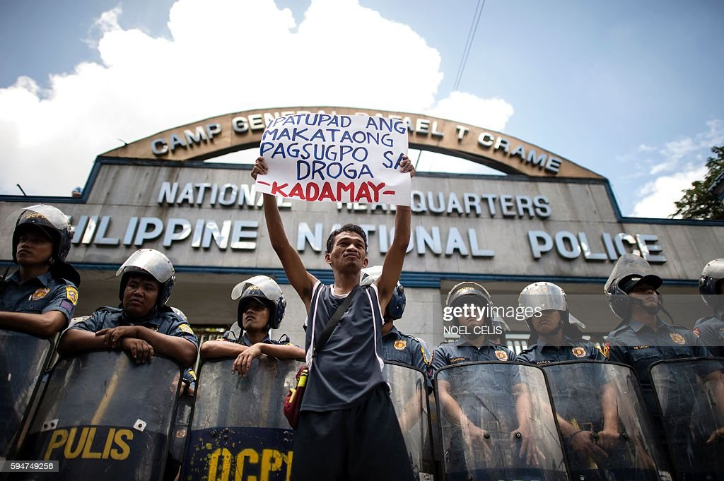 A activist hold a banner in front of Philippine National Police headquarters during a protest condemning what they call extrajudicial killings...