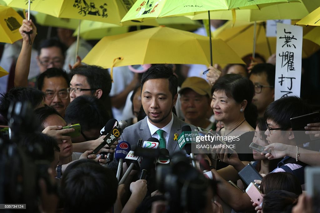 Activist Ken Tsang (C) speaks to the media outside the Kowloon city court after being sentenced to five weeks in prison for assaulting police during the 2014 pro-democracy protests, in Hong Kong on May 30, 2016. A Hong Kong pro-democracy activist who was allegedly beaten by police in an attack captured by television cameras and beamed around the world was given a five-week jail term on May 30 of assaulting and resisting police officers. / AFP / ISAAC