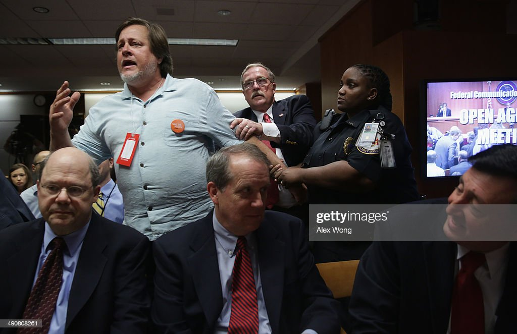 Activist Kevin Zeese (L) is pulled away as he protests during an open meeting to receive public comment on proposed open Internet notice of proposed rulemaking and spectrum auctions May 15, 2014 at the Federal Communications Commission (FCC) headquarters in Washington, DC. The FCC has voted in favor of a proposal to reform net neutrality and could allow Internet service providers to charge for faster and higher-quality service.