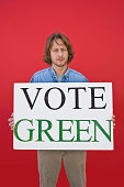 Activist man holding vote green sign