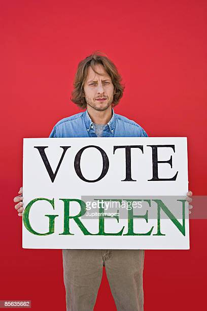 Activist man holding vote green sign