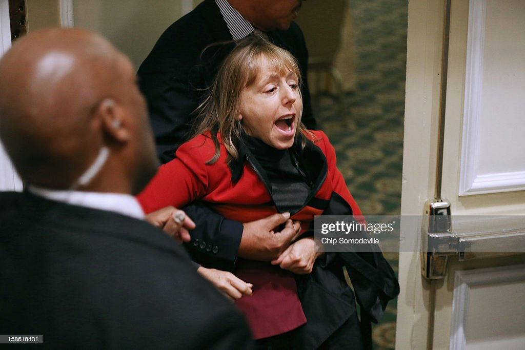 Activist Medea Benjamin of CodePink is carried away by security guards after interrupting a National Rifle Association news conference at the Willard Hotel December 21, 2012 in Washington, DC. This is the first public appearance that leaders of the gun rights group have made since a 20-year-old man used a popular assault-style rifle to slaughter 20 school children and six adults at Sandy Hook Elementary School in Newtown, Connecticut, one week ago.