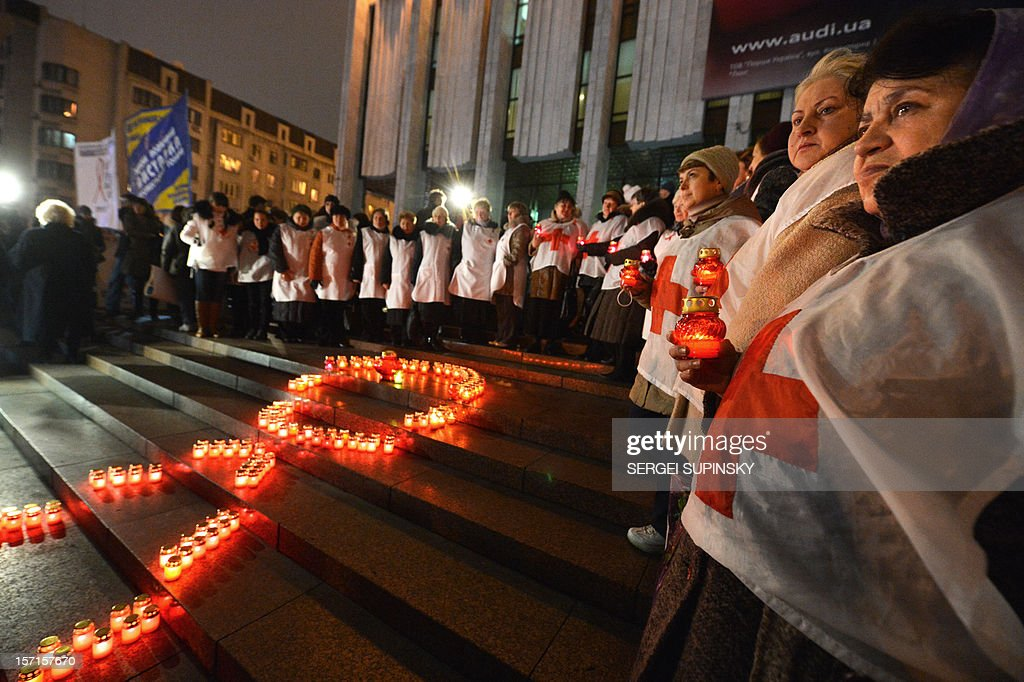 Activist of public organizations and HIV infected people holds candles as they rally in front of a Red Ribbon set with candles in the center of the Ukrainian capital of Kiev on November 29, 2012 to mark the upcoming World AIDS Day on December 1. Ukraine has one of the fastest growing HIV/AIDS epidemics in the world.AFP PHOTO/ SERGEI SUPINSKY