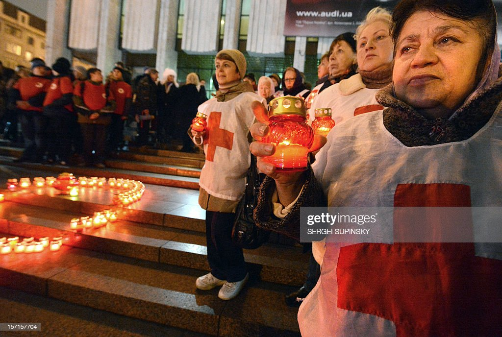 Activist of public organizations and HIV infected people holds candles as they rally in front of a Red Ribbon set with candles in the center of the Ukrainian capital of Kiev on November 29, 2012 to mark the upcoming World AIDS Day on December 1. Ukraine has one of the fastest growing HIV/AIDS epidemics in the world.