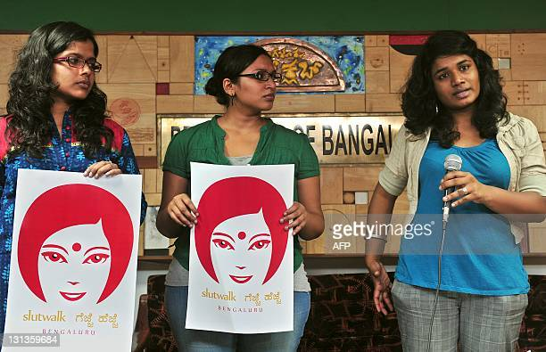 Activist of 'SlutWalk Bengaluru Gejje Hejje' hold campaign posters while another gestures how women become victims of sexual harrasment on streets...