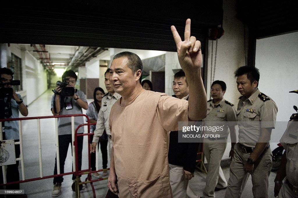 Activist Somyot Prueksakasemsuk reacts as he arrives at the criminal court in Bangkok on January 23, 2013. A prominent Thai political activist accused of insulting the monarchy was handed an 11-year prison term in the latest tough sentence under the kingdom's lese majeste laws. The Criminal Court in Bangkok convicted Somyot Prueksakasemsuk in connection with two articles deemed offensive to the royal family that were published by a magazine he edited at the time. AFP PHOTO/ Nicolas ASFOURI