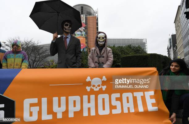 Activists acting as Monsantocharacters with their faces painted with skulls take part in an action calling for the EU Commission to vote against the...