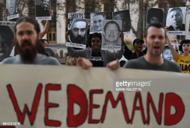 Activists and community members hold photographs of nearly 300 people who they say have been killed by police in the Los Angeles area as they march...