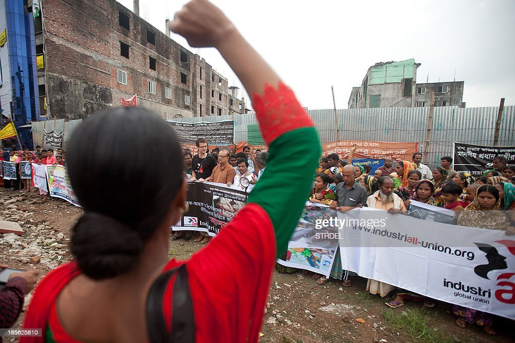 Activists and survivors of the Rana Plaza garment factory disaster demonstrate on the site where the building collapsed in Savar, on the outskirts of Dhaka, on October 23, 2013. The activists gathered on the eve of the 6-month anniversary of the disaster that killed 1,132 people and highlighted the industry's poor safety standards.