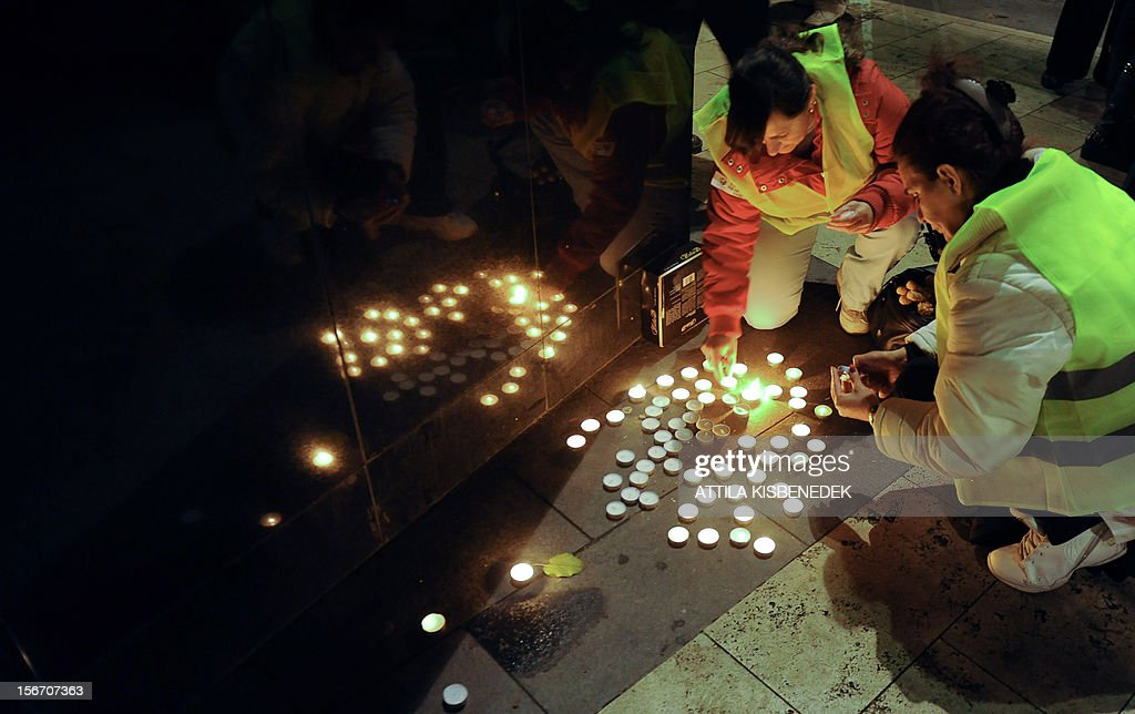 Activists and sympathizers of a Hungarian parliament party, the 'Democratic Coalition' light candles beside the 'Monument of 1956 Revolution' in front of the parliament building in Budapest on November 19, 2012 during their demonstration of the Life Chain' to protest against the plan of the new election law.