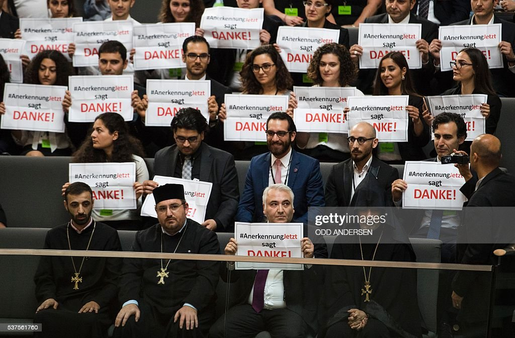 Activists and the leader of the Anerkennung Jetzt (Recognition Now) civil society initiative, Ilias Uyar (Bottom C), react after law makers voted to recognise the Armenian genocide after a debate during the 173rd sitting of the Bundestag, the German lower house of parliament, in Berlin on June 2, 2016. #RecognitionNow says Thanks! / AFP / ODD