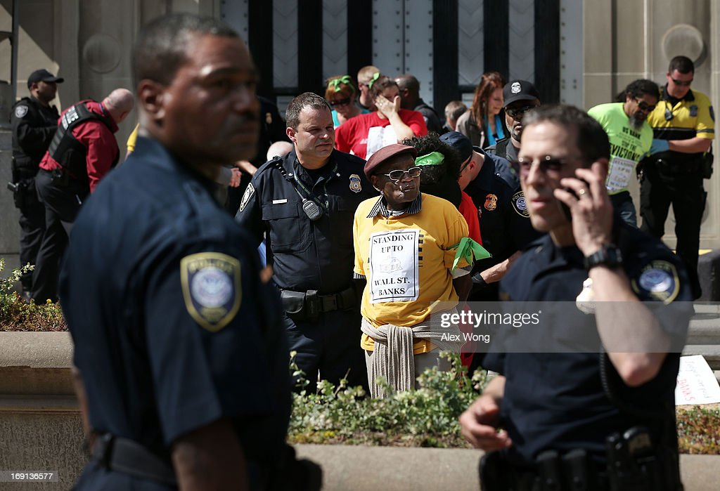 Activists are arrested by the police after they participated in civil disobedience during a protest outside the U.S. Justice Department May 20, 2013 in Washington, DC. Homeowners and activists from Home Defenders League and Occupy Homes joined the protest to demand that Attorney General Eric Holder 'hold Wall Street Banks that ravaged America's economy accountable.'