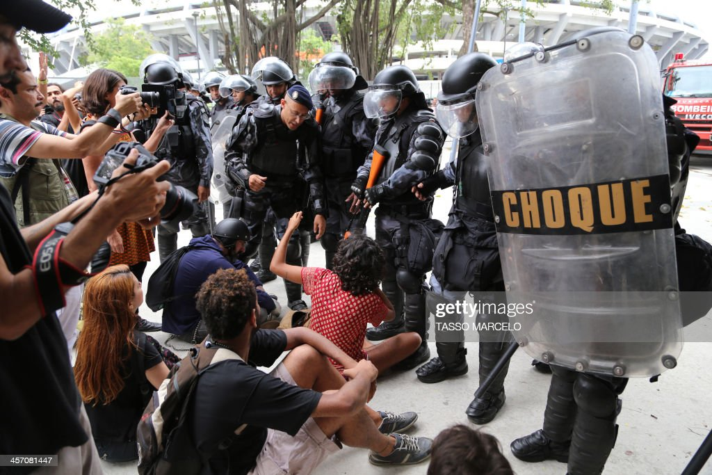 Activists are detained by riot police during a demonstration near the Museu do Indio (Indian Museum) 'Aldea Maracana' (Maracana Village) in Rio de Janeiro, Brazil, on December 16, 2013. The demonstrators, among whom there were some 30 Amazonic natives, seized the museum protesting against its scheduled demolition to continue the works in the Mario Filho 'Maracana' stadium ahead of the FIFA WC Brazil 2014.