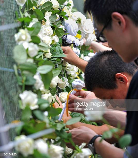 Activists attach white roses to an iron gate outside Taiwan's parliament in Taipei on July 31 2011 during a rally to push for an amendment to the...