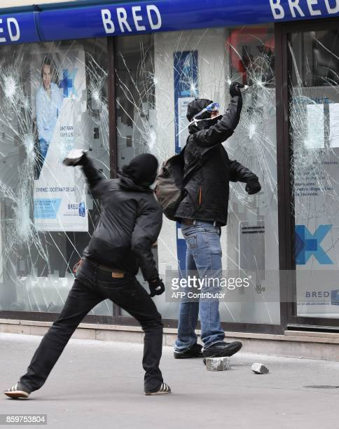Activists attack the front window of a Bred bank branch on the sidelines of a demonstration on October 10 2017 in Paris as part of a nationwide...