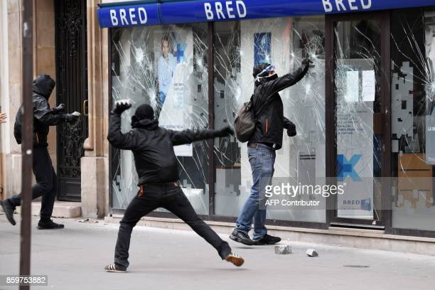 TOPSHOT Activists attack the front window of a Bred bank branch on the sidelines of a demonstration on October 10 2017 in Paris as part of a...