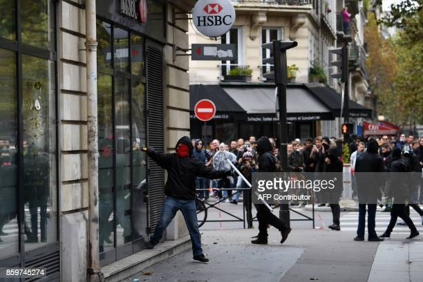 Activists attack the front window of a Swiss bank HSBC branch on the sidelines of a demonstration on October 10 2017 in Paris part of a nationwide...
