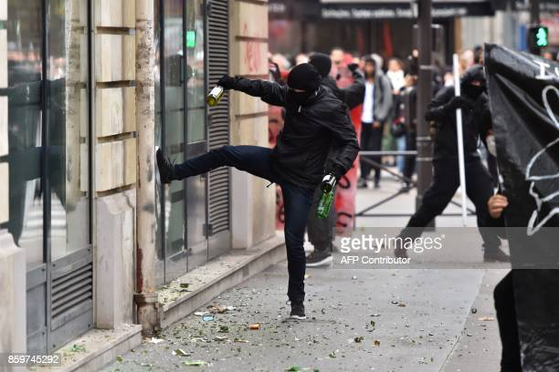 TOPSHOT Activists attack the front window of a Swiss bank HSBC branch on the sidelines of a demonstration on October 10 2017 in Paris part of a...