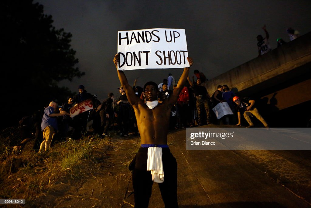 Activists attempt to make their way onto Interstate 277 to block traffic as they march in the streets amid a heavy police and National Guard presence as they protest the death of Keith Scott September 22, 2016 in Charlotte, North Carolina. Scott, 43, was shot and killed by police officers at an apartment complex near UNC Charlotte.