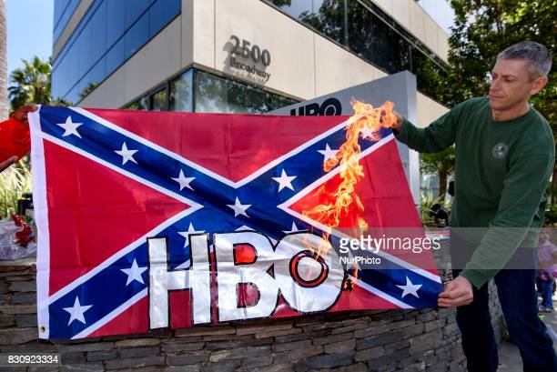 Activists burn a Confederate flag with the HBO logo in protest of HBOs new series in development Confederate Santa Monica California on August 12...