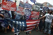 Activists burn a mock US flag during a protest at the US embassy to coincide with US Secretary of State John Kerry's visit to the Philippines in...