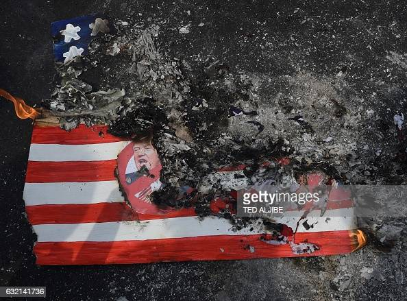 TOPSHOT Activists burn a mock US flag with Presidentelect Donald Trump's portrait during a rally in front of the US embassy in Manila on January 20...