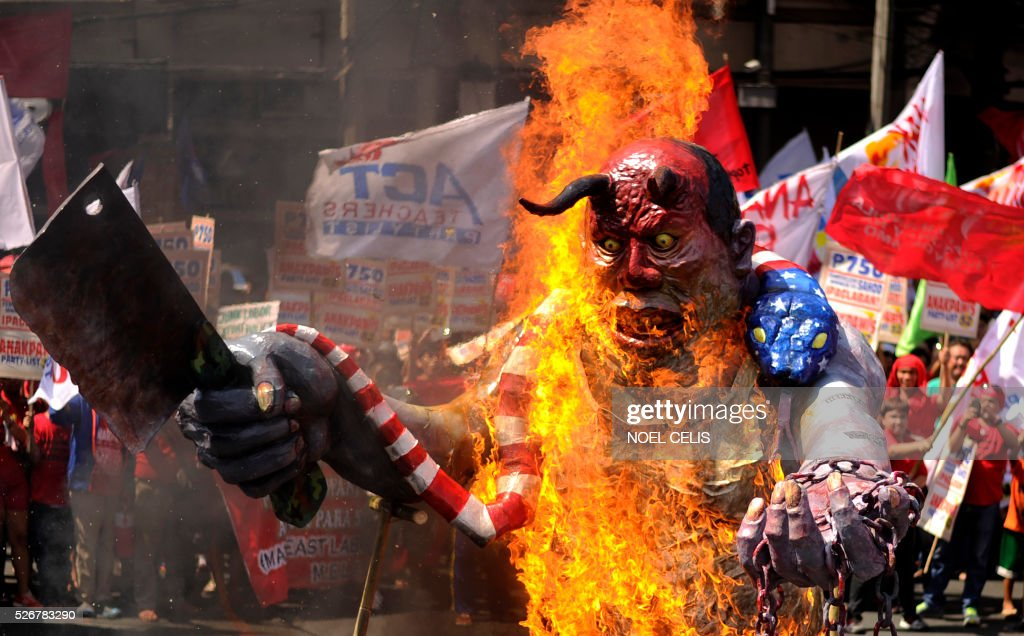 Activists burn an effigy of Philippine President Benigno Aquino during the Labor Day Protest near the Malacanang Palace in Manila on May 1, 2016. Thousands of workers and activists marched on Philippine streets marking May Day to protest the government's migrant labour policy and demand higher wages amid rising prices for basic commodities. / AFP / NOEL