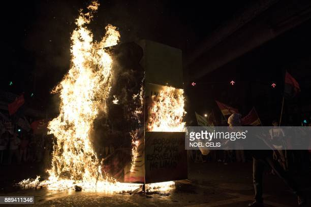 Activists burn an effigy of Philippine President Rodrigo Duterte during a protest in Manila on December 10 as they commemorate the International...