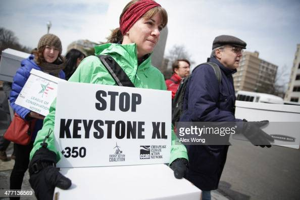 Activists carry signs and petition boxes as they march to the State Department for a rally to protest against the Keystone XL pipeline March 7 2014...