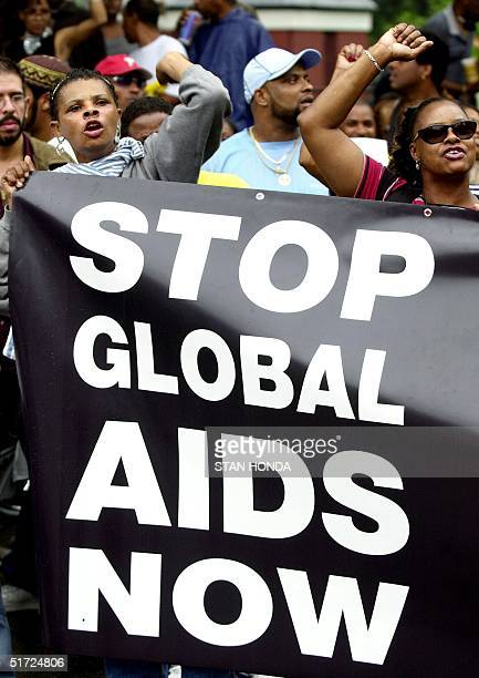 AIDS activists church groups and antidebt activists shout slogans as they rally in New York's Washington Square Park 23 June 2001 Several hundred...