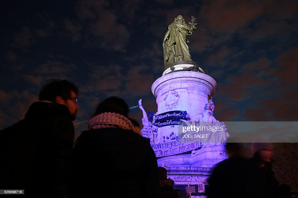 Activists climb onto the monument at the center of the Place de la Republique to unfold banners during the Nuit Debout, or 'Up All Night' movement on April 28, 2016 in Paris. The 'Nuit Debout' demonstrations began on March 31 in opposition to the government's proposed labour reforms. Banners read 'Where are you Democracy ?', 'Borders are killing' and 'Solidarity with the migrants'.