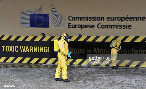 """Activists demonstrate in front of a banner reading """"toxic warning"""" outside the Commission headquarters on November 7 2012 at the EU headquarters in..."""