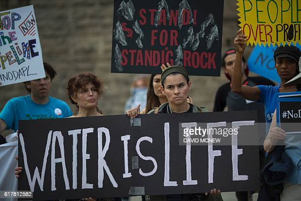 Activists demonstrate near a Hillary Clinton presidential campaign fundraiser featuring US President Barack Obama to call for a halt to the Dakota...