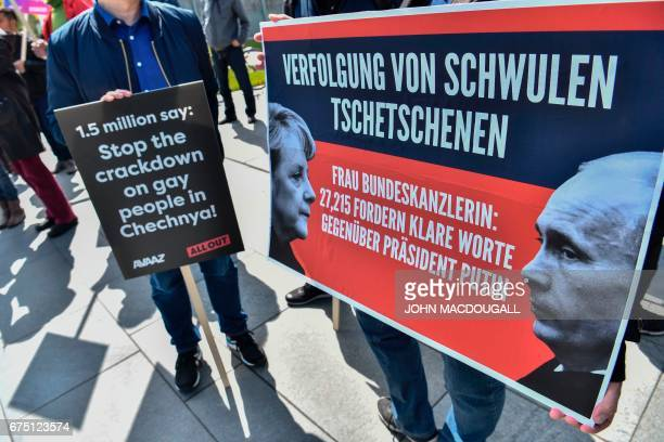Activists display placards in front of the Chancellery in Berlin on April 30 during a demonstration calling on Russian President to put an end to the...