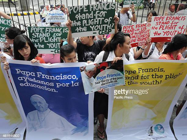 Activists display postcards and tarpaulins with the image of Pope Francis in front of the University of Santo Tomas as they celebrate the forthcoming...