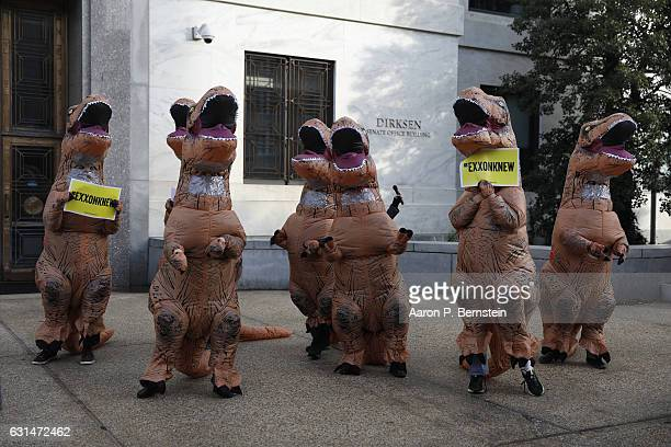 Activists dressed as dinosaurs rally against former ExxonMobil CEO and Secretary of State nominee Rex Tillerson outside Dirksen Senate Office...