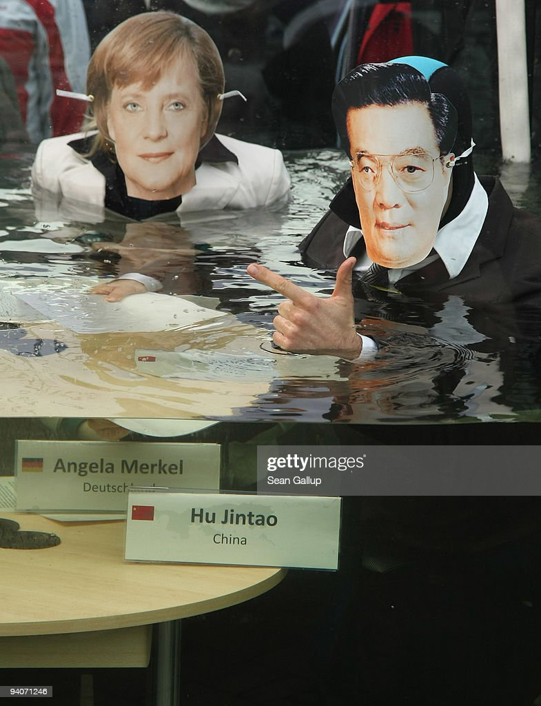 Activists dressed as leaders Chancellor <a gi-track='captionPersonalityLinkClicked' href=/galleries/search?phrase=Angela+Merkel&family=editorial&specificpeople=202161 ng-click='$event.stopPropagation()'>Angela Merkel</a> of Germany and President Hu Jintao of China pretend to debate in a giant aquarium filling with water on December 5, 2009 in Berlin, Germany. The activists were hoping to raise awareness for the need for rapid action on global warming ahead of the upcoming international conference on climate change in Copenhagen.