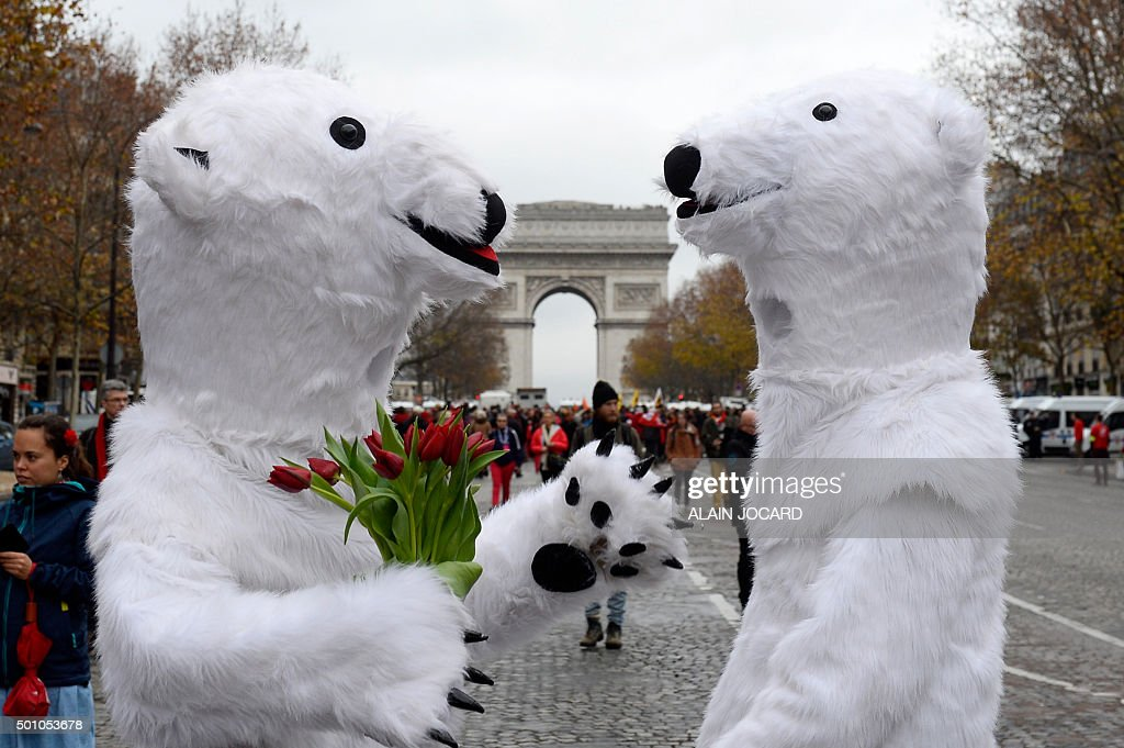 TOPSHOT - Activists dressed as polar bears are pictured as activists gather for a demonstration to form a giant red line at the Avenue de la Grande armee boulevard in Paris on December 12, 2015, as a proposed 195-nation accord to curb emissions of the heat-trapping gases that threaten to wreak havoc on Earth's climate system is to be presented at the United Nations conference on climate change COP21 in Le Bourget, on the outskirts of Paris. / AFP / ALAIN