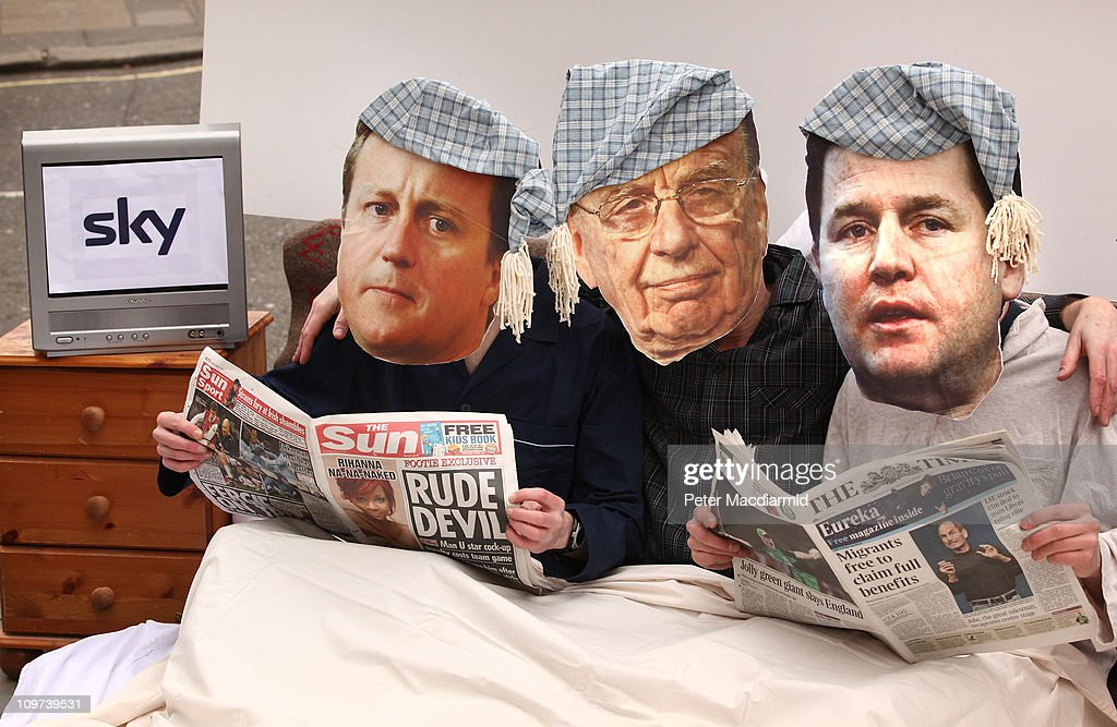 Activists dressed as Prime Minister <a gi-track='captionPersonalityLinkClicked' href=/galleries/search?phrase=David+Cameron+-+Politician&family=editorial&specificpeople=227076 ng-click='$event.stopPropagation()'>David Cameron</a> (L), News Corporation owner Rupert Murdoch and Deputy Prime Minister Nick Clegg share a bed in a stunt outside a media and broadcasting conference on March 3, 2011 in London, England. The British government has given the go-ahead for Rupert Murdoch's News Corporation to takeover satellite broadcaster BSkyB. The deal has been allowed after News Corporation offered to spin off Sky's news division into a seperate company.