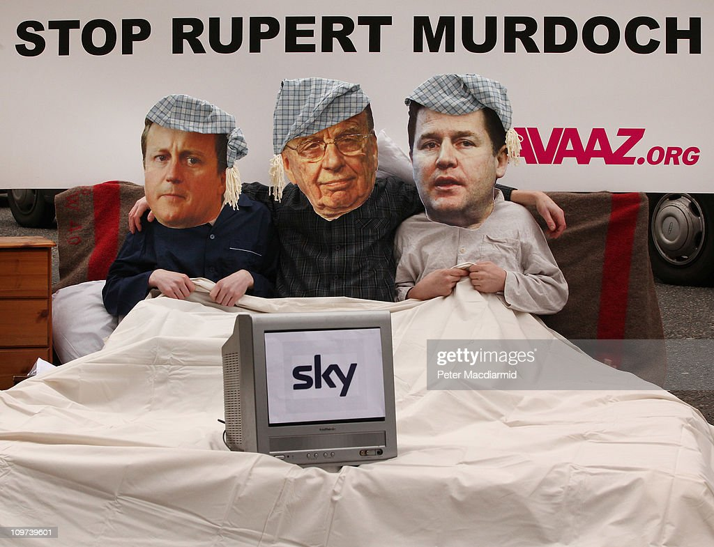 Activists dressed as Prime Minister <a gi-track='captionPersonalityLinkClicked' href=/galleries/search?phrase=David+Cameron+-+Politician&family=editorial&specificpeople=227076 ng-click='$event.stopPropagation()'>David Cameron</a> (L), News Corporation owner Rupert Murdoch and Deputy Prime Minister Nick Clegg (R) share a bed in a stunt outside a media and broadcasting conference on March 3, 2011 in London, England. The British government has given the go-ahead for Rupert Murdoch's News Corporation to takeover satellite broadcaster BSkyB. The deal has been allowed after News Corporation offered to spin off Sky's news division into a seperate company.
