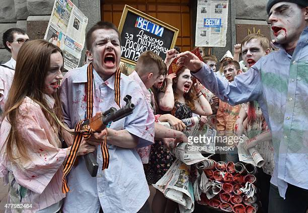 Activists dressed as zombies to represent consumers of proRussian propaganda hold the free proRussian newspaper 'Vesti' distributed in Ukraine during...