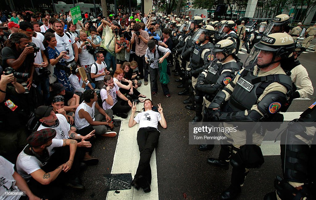 Activists face off with law enforcement officers while demonstrating on August 27, 2012 in Tampa, Florida. The demonstration was being held just before of the start of the Republican's nominating convention which will hold its first session on August 28. The convention was scheduled to start on August 27 but was pushed back one day as Tropical Storm Isaac threatens to hit the Tampa area.
