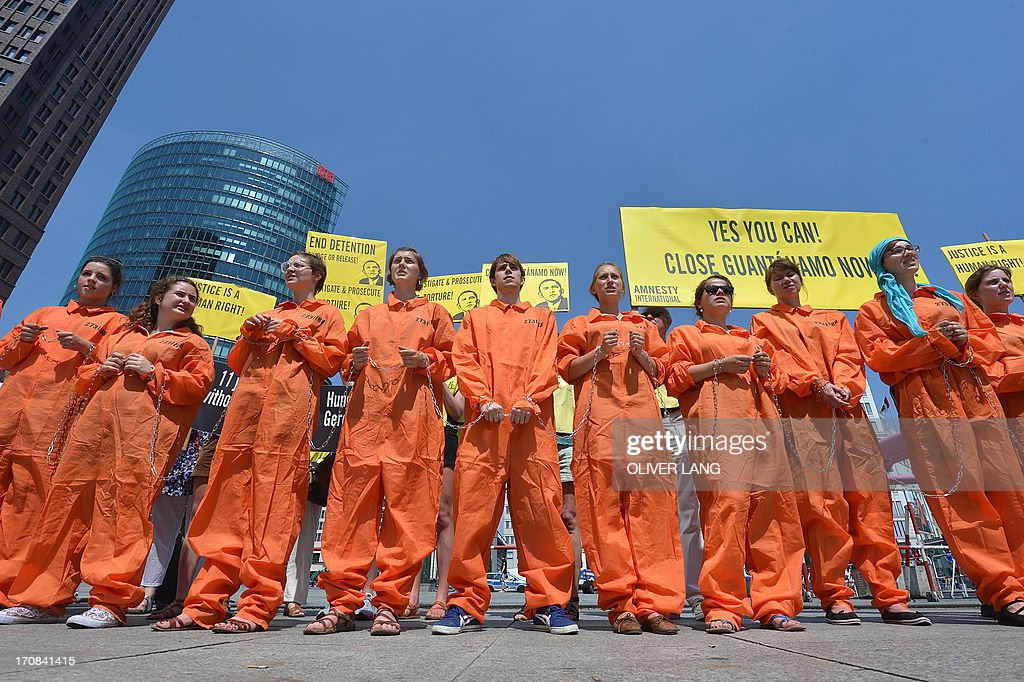 Activists from Amnesty International human rights association wear orange uniforms and chains like Guantamo detainees wear during a protest action on the Potsdamer Platz in Berlin, on June 19, 2013 where US President has his hotel during his official visit. Protestors urged US President Barack Obama Wednesday to close the Guantanamo Bay military jail in the first of a scattering of demonstrations on myriad issues planned at Berlin landmarks for his landmark 24-hour visit. Banners read 'Yes you can! Close Guantanamo now'. LANG