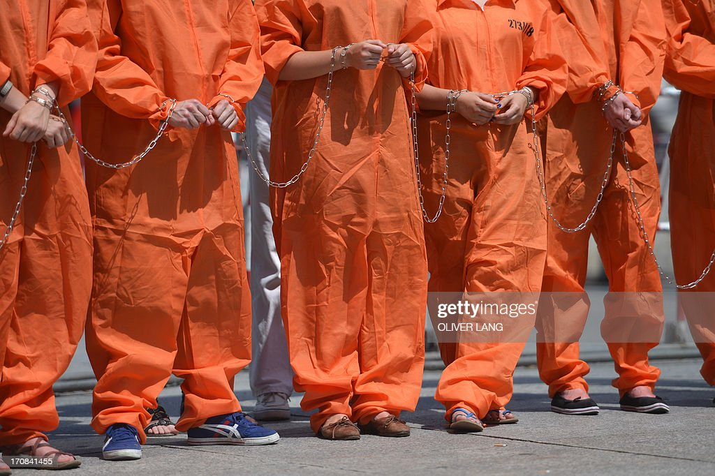 Activists from Amnesty International human rights association wear orange uniforms and chains like Guantamo detainees wear during a protest action on the Potsdamer Platz in Berlin, on June 19, 2013 where US President has his hotel during his official visit. Protestors urged US President Barack Obama Wednesday to close the Guantanamo Bay military jail in the first of a scattering of demonstrations on myriad issues planned at Berlin landmarks for his landmark 24-hour visit. LANG