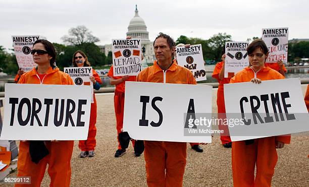 Activists from Amnesty International protest holding signs 'torture is a crime' near the US Capitol on April 30 2009 in Washington DC The protesters...