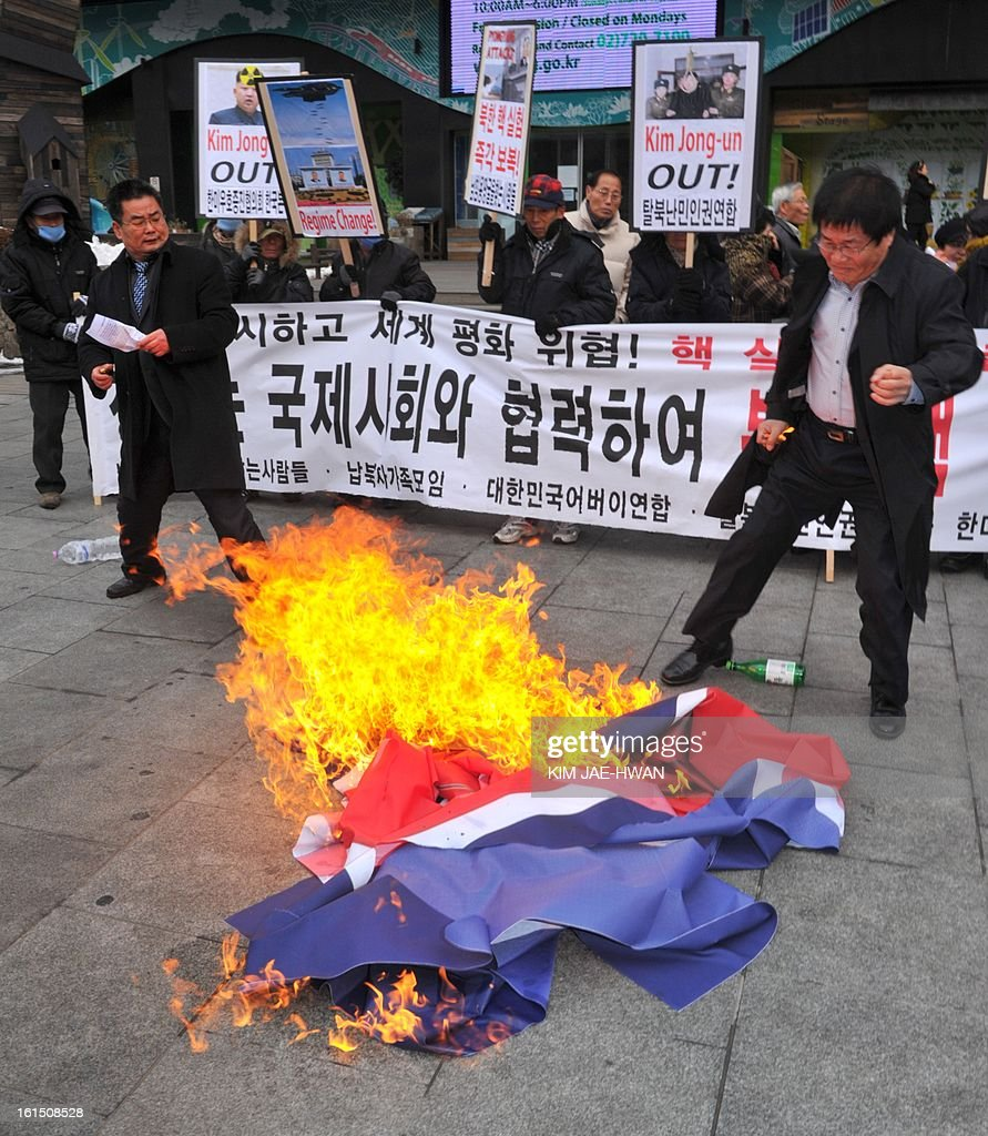 Activists from an anti-North Korea civic group burn a North Korea national flag during a rally in Seoul on February 12, 2013. North Korea on February 12 staged its most powerful nuclear test yet, claiming a technological breakthrough with a 'miniaturised' device in a striking act of defiance to global powers including its sole patron China. AFP PHOTO / KIM JAE-HWAN